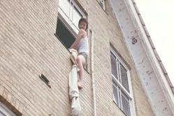シーツでロープを作り窓から逃げようとする梨里