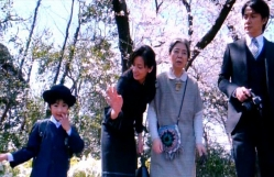 慶多の小学校の入学式でハンディカメラに撮られている野々宮の家族