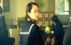 振り返って窓の外のいる教師の村田を見る萩本小鳩