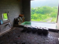温泉棟、大窓からは渓流越しの山々がお湯に鏡にと見える。