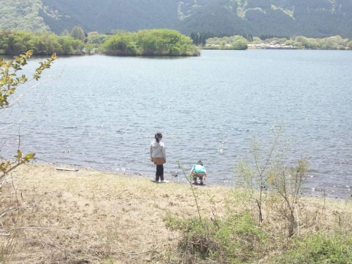 湖畔の波打ち際で遊ぶ幼い姉弟は美しい